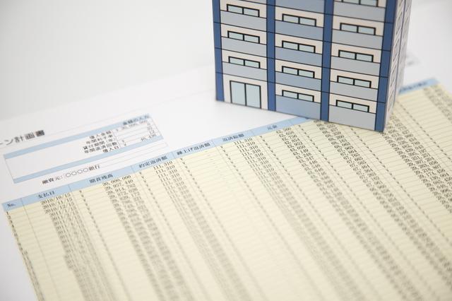 請求書とその上の紙のマンション模型